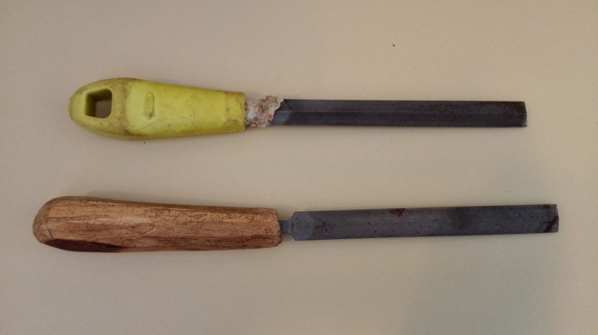 To identiske sverdfiler. Den eine med heimelaga treskaft, den andre med gult plastskaft. På denne er det surra papir i feste, for at fila skal sitja betre.  Kvar side er forhøga på midten , slik at det vert fire slipeflater. Vanleg nemning på slik fil er sverdfil.