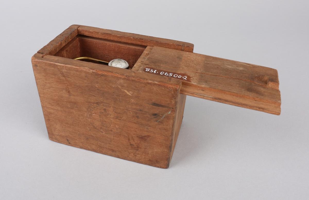 Liten vekt inne i rund beholder av messing med vatermerke på utsiden av beholder med håndtak. Ligger i liten treeske med løst lokk.