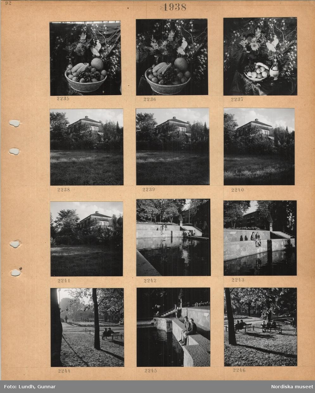 Motiv: Korg med frukt, blommor, vinflaska framför ett draperat tyg, större villa(?) i lummig trädgård, lekande barn vid rektangulär damm, park, flerbostadshus i bakgrunden, murar, trappa, två kvinnor sitter på en parkbänk, i bakgrunden byggnader, två flickor sitter på en mur vid damm.