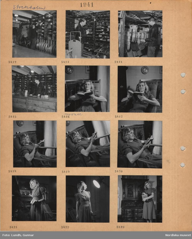 Motiv: Stockholm, butikslager(?), man i skyddsrock hanterar varor i hyllor, kabel av olika dimension, spadar, skyfflar m.m., modell klädd i klänning sitter i en stol och läser en bok, står med bok i handen, håller i en låda.
