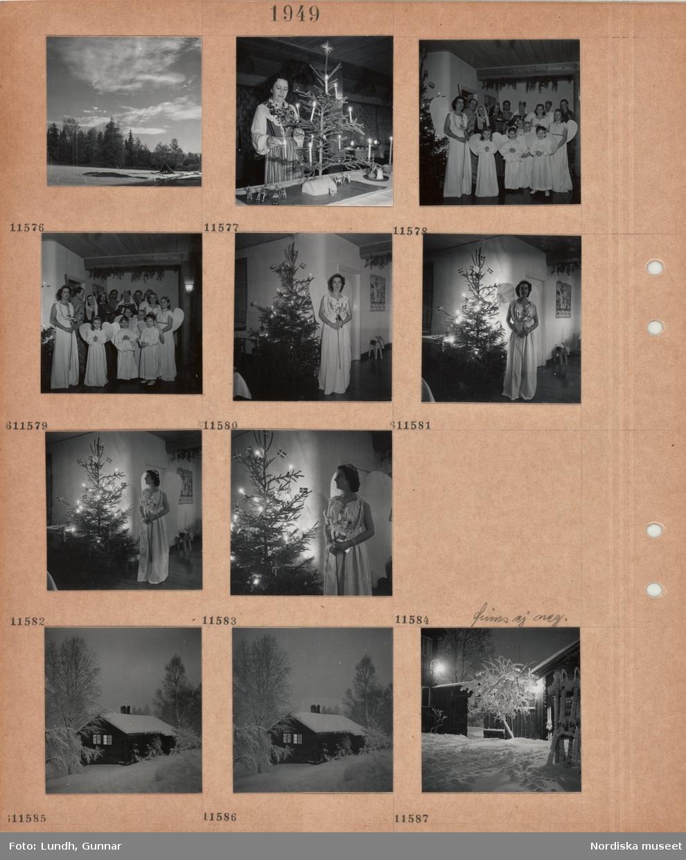 Motiv: Sluttning med träd i snö, kvinna i folkdräkt tänder ljus i en bordsgran, barn och vuxna klädda för julspel, kvinna klädd till ängel bredvid pyntad julgran, timmerhus i snö, träd, gårdsplan i snö.