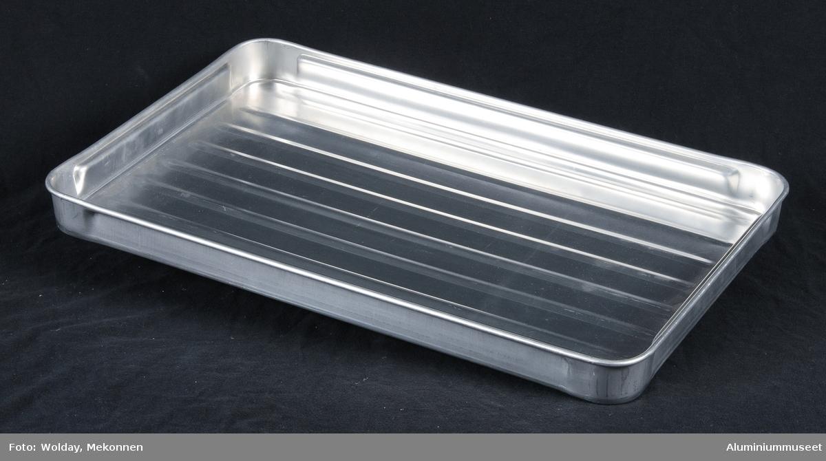 Teknikk: Brettet er presset med riller i bunn, i ett trekk i store presse. ( M.nr. 99. Se bilde nr 13.) Brettet er skjegget og falset i store presse. Kombinert håndtak og stablevuls er presset i fire operasjoner i eksenterpresse. Form: Lavt firkantet brett