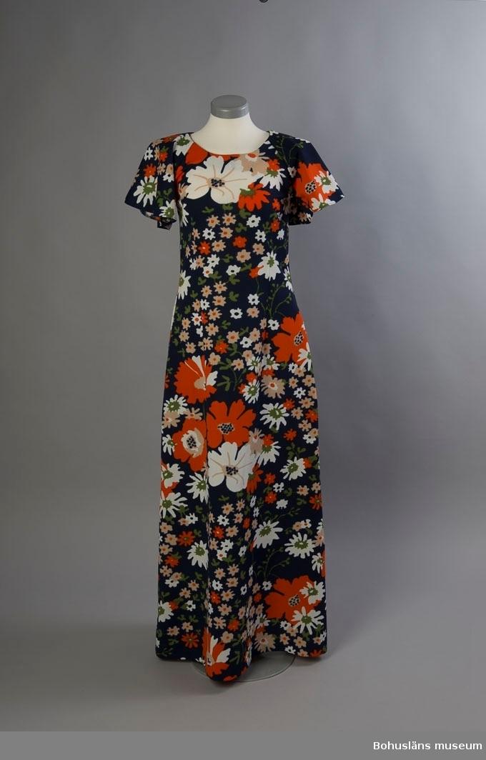 """Hellång klänning med kort volangärm i strechande konstmaterial med kraftigt blommönster i orange, vitt, grönt och beige på mörkblå botten.  Enkelt framstycke  med 30 cm långa insparningar under bysten samt bystveck. Bakstycke i två delar med mittsöm och lång, dold dragkedja. Rund halsringning där ärmens överstycke utgör del av ringningen. Ärmen i ett stycke, sammansydd med söm undertill.   Ofodrad. Etikett i halslinningen med med texten: """"MAGNA SWEDISH DESIGN"""", STORLEK 40.    ."""