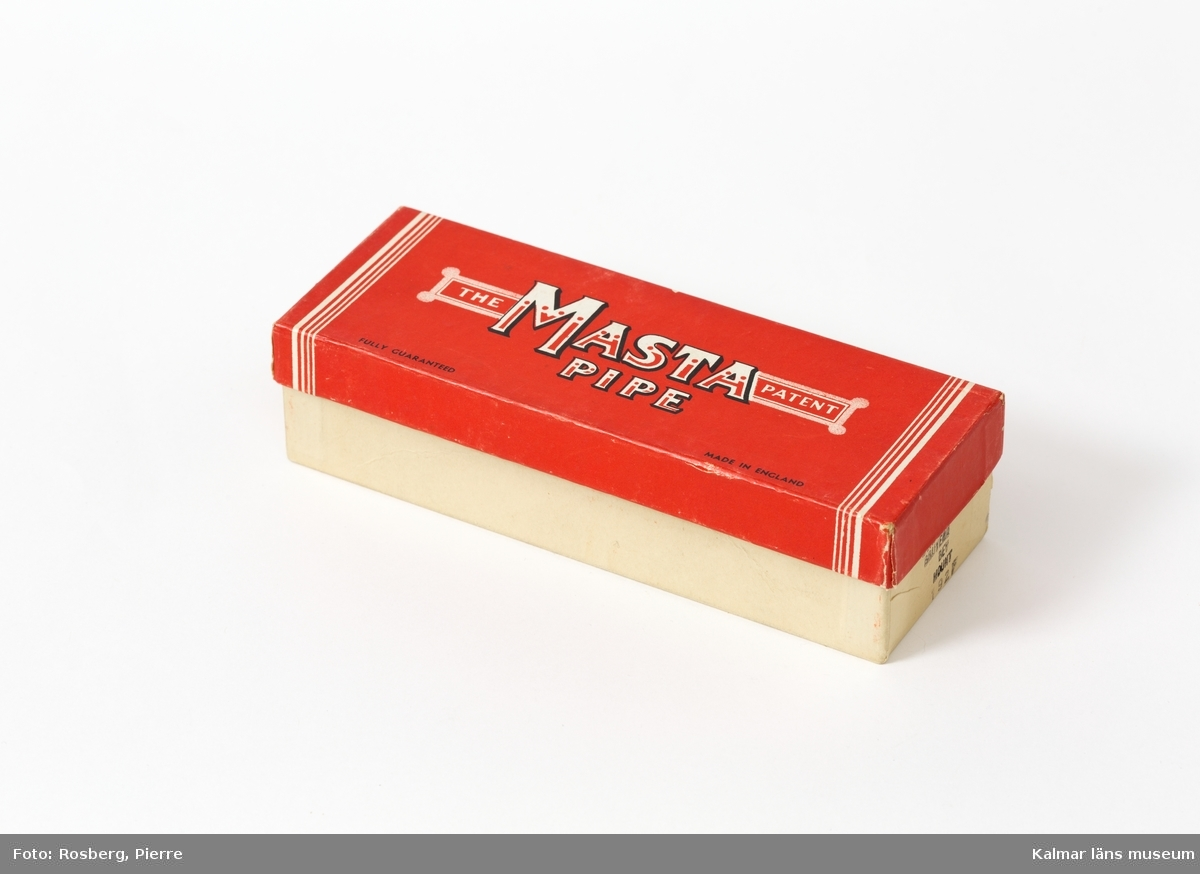 KLM 45058:4:1-2. Pipa i originalförpackning. Pipa av trädljung/briar, förpackning av papp. :4:1 Pipa med rakt, svart munstycke av okänt material och brunt, polerat, rundat piphuvud. :4:2 Förpackning, vit med rött lock med text i vitt, svart och rött. Text: The Masta Pipe patent.
