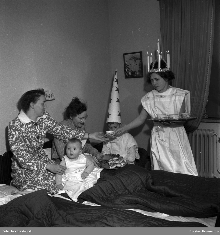 Luciafirande hemma hos familjen Berg. En pojke och en flicka lussar för två kvinnor och ett litet barn.