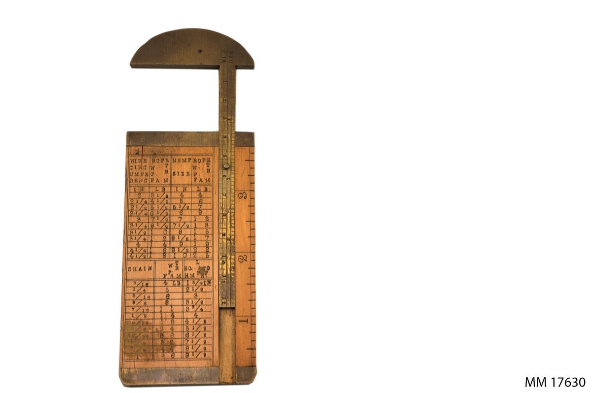 """Målsticka av ljust fernissad träplatta, kanterna och målstickan i mässing. Översta delen rundad samt fästad till måttstickan. Måttstickan löper i ett spår på träplattan. På stickan finns scheman som visar tågvirkes dimensioner samt olika måttenheter; omkrets, inch, pound och så vidare. text och siffror stansade för hand. På stickans kant märkt : """" FRANCIS REILY & Co WARRANTED BETS BOX """"."""