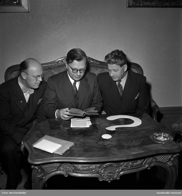 Frågesport i Stadshussalongen, tre män runt ett bord med ett frågetecken på.