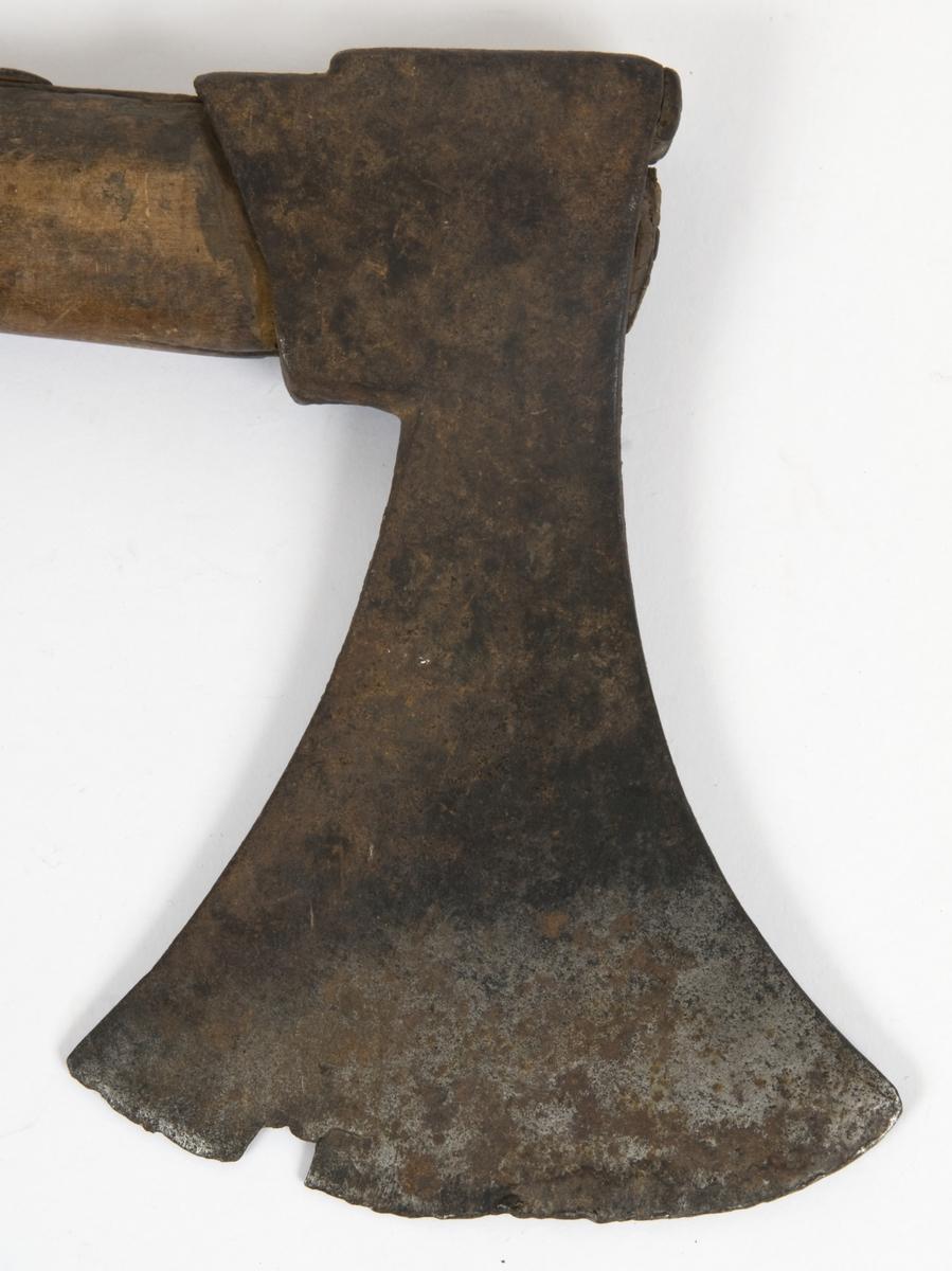Asymmetrisk blad med lang øvre spiss og kortere nedre spiss. Bladet er klieformet..  Øksehammeren har skaftehull  Gammelt skaft med ryggskinne og benring med risset dekor nederst.