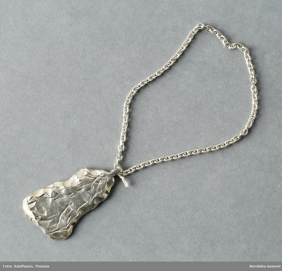 """Catelaine i form av hänge i silver i asymmetrisk avlång form, slät på baksidan, upptill ögla i vilken sitter en sluten silverkedja. På baksidan av hänget stämplat """"All_Blues"""" samt stadsstämpeln för Stockholm St Eriks-stämpeln och """"925"""" [anger silverhalten] /Leif Wallin 2015-02-10"""