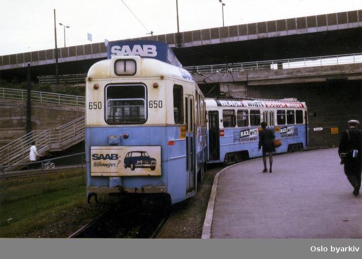 """Oslo Sporveier. Tilhenger type TO nr. 650 kalt """"Stivkjelke"""" på linje 1, Sinsen-Majorstuen. Reklame for Saab og Martini. Konduktørskifte på Sinsen endeholdeplass."""