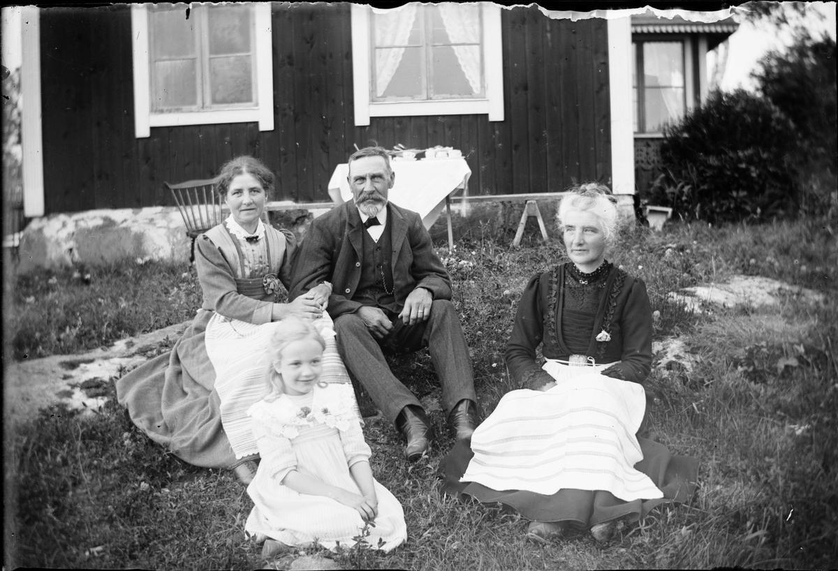 En man, två kvinnor och en flicka sitter i gräset vid bostadshuset, Östhammar, Uppland