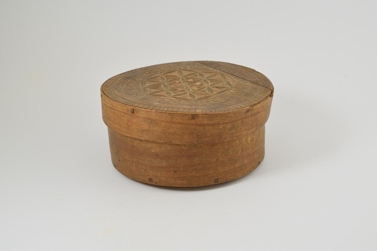Sirkelformet eske i tre, med lokk. Dekorert med karveskurd på toppen av lokket, motivet er seks-bladsroser, ellers ingen dekor. Sveipet og festet med røtter siden.