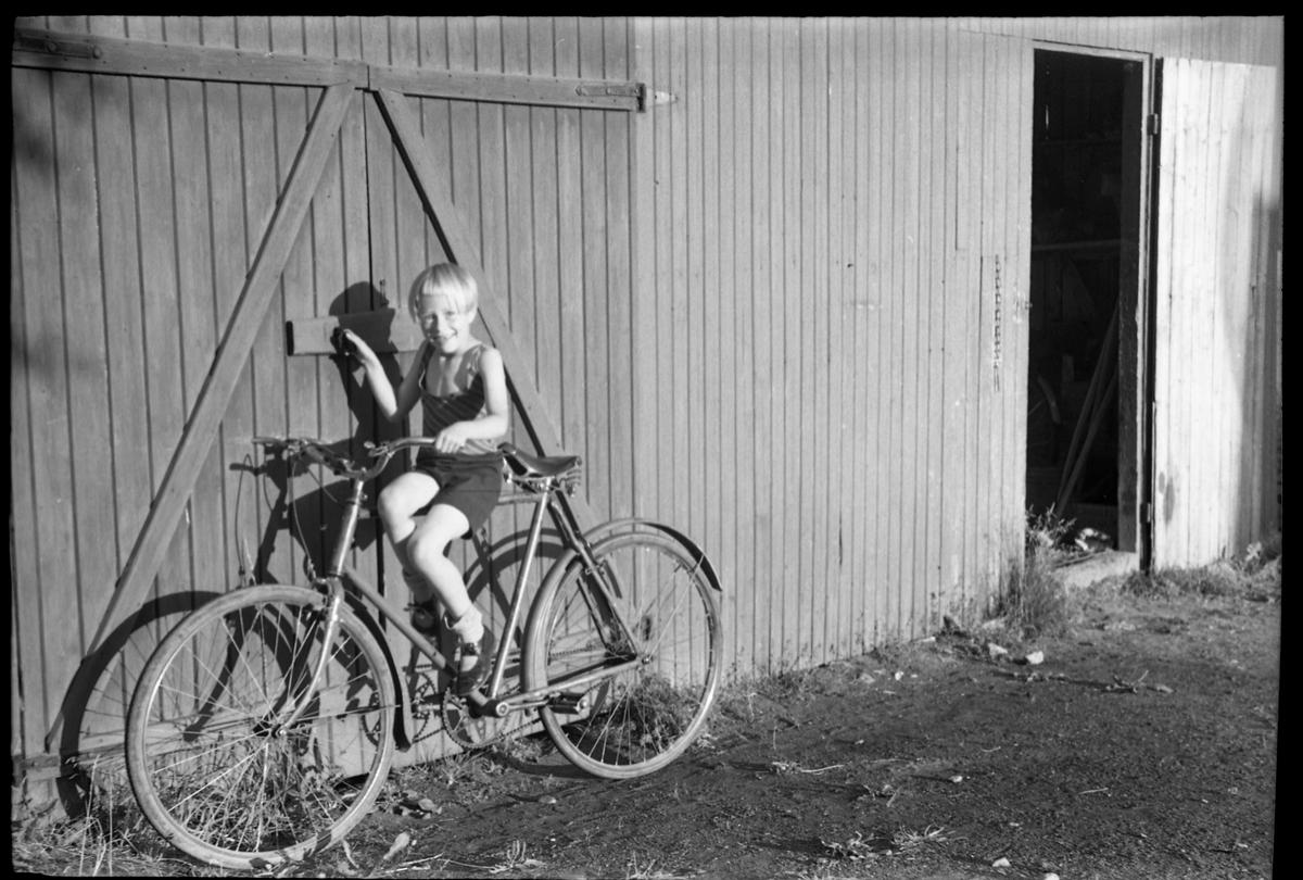 Sigrun Røisli på sykkel ved uthuset hjemme på Odberg på Kraby, Ø.Toten.