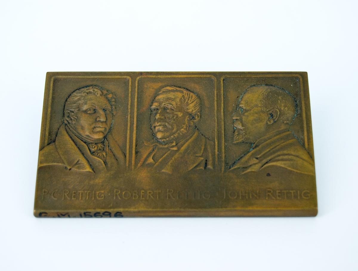 Rettigska fabriken och Rettigska palatset på plakettens ena sida. Tre generationer Rettig på den andra. P.C Rettig, Robert Rettig och John Rettig.