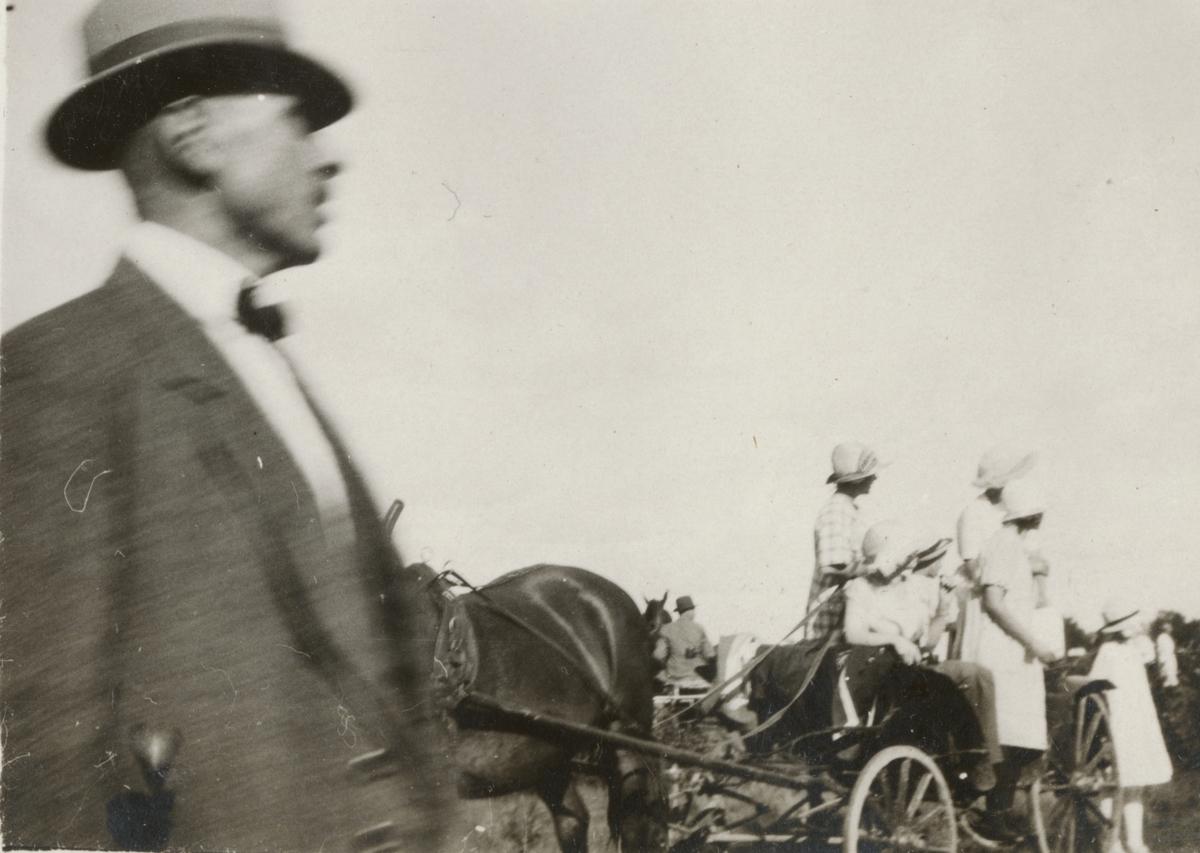 Civila kvinnor och män bland hästar och vagn.