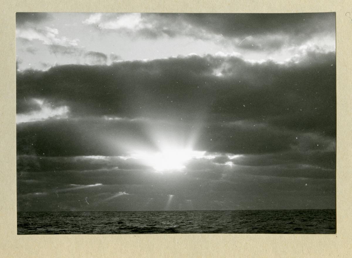 Bilden föreställer horisonten, där solens strålar skiner igenom ett molntäcke. Bilden är tagen i samband med minfartyget Älvsnabbens långresa 1966-1967.