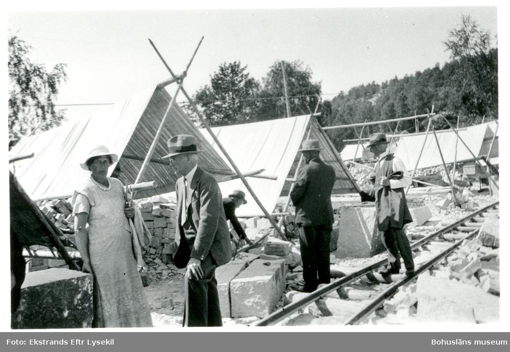 Fyra män i kostym och hatt samt en kvinna i klänning och pärlhalsband går runt på ett stenhuggeri, solen lyser och två av personerna bär sina kavajer över armen. I bakgrunden står ställningar övertäckta av dukar, troligen för att ge stenhuggarna skugga under arbetet
