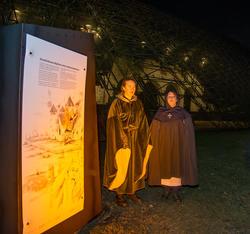To kvinner i middelalderklær og kapper står foran en svakt opplyst middelalderruin og synger.