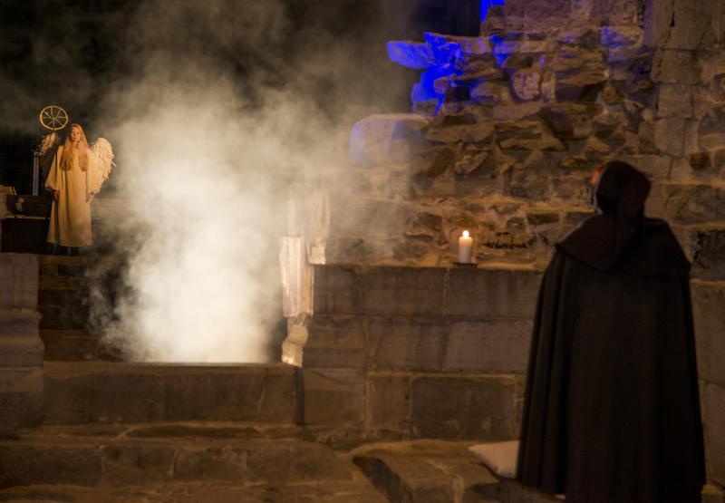 En mørk skikkelse i kappe ser fram mot en hvit engel som står i lys og røyk.