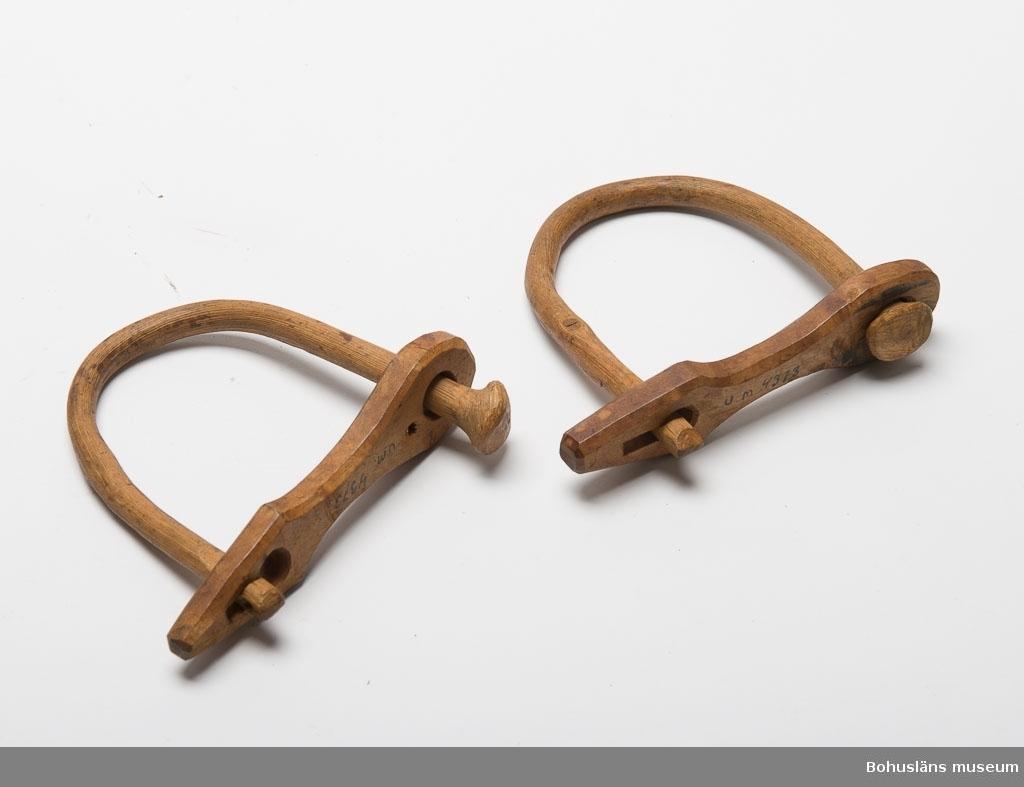 Böjd (basad gren). Ena sidan är fäst i ett runt hål i en träbricka. Den andra sidan är instoppad i ett nyckelhålsformat hål i samma bricka. Denna sida går att öppna. Träbrickan är fasad.  Ur handskrivna katalogen 1957-1958: Två fårklavar L. 15, Br. 13,5. L. 14,5 Br. 14. Av trä. Föremålen. Bohuslän