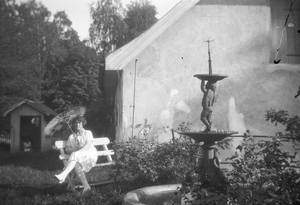 Kvinne på benk i hagen.