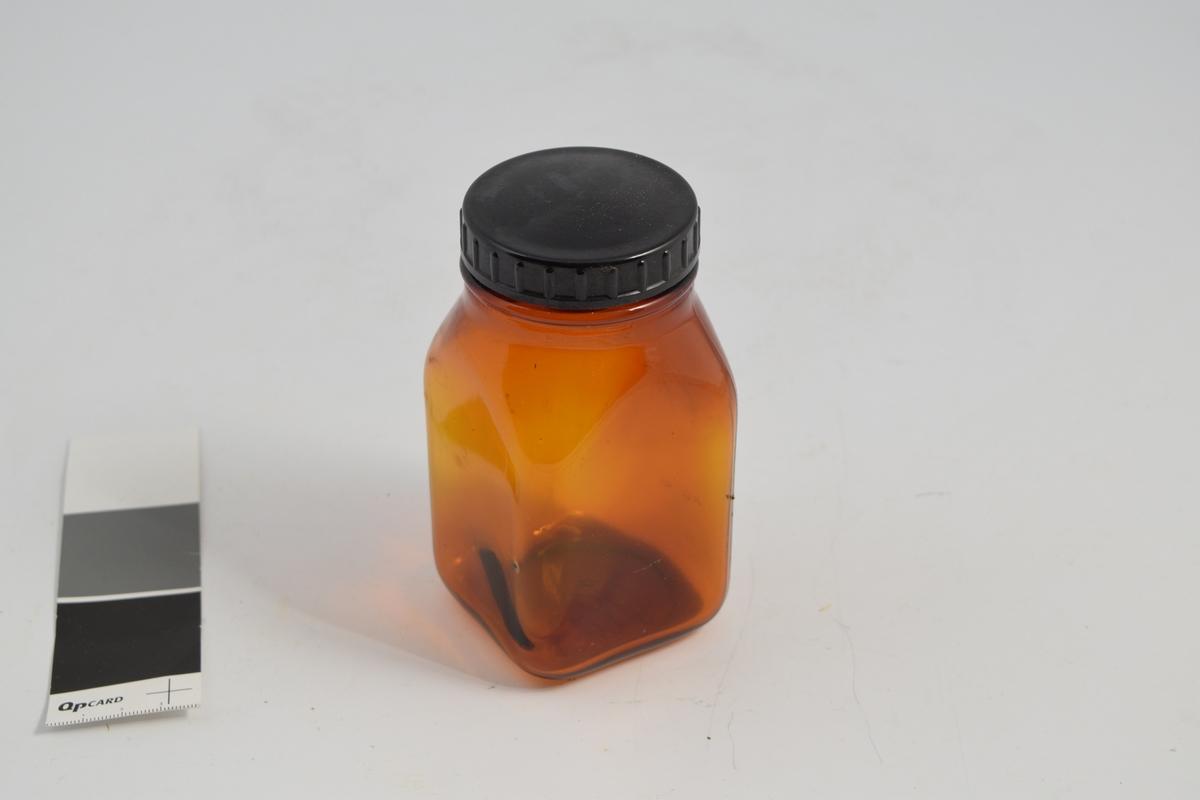 5 stk. apotekerflasker m/skrukork. Brunt glass, firkantet bunn, sort rundt bakelittlokk med skrugjenger. Glassene ble brukt til oppbevaring av tabletter og eventuelt til slag av større mengder.