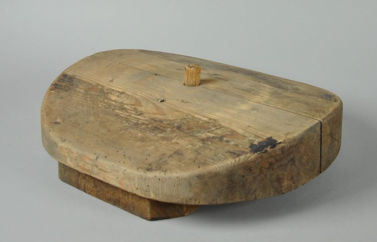 Oval bremblokk med oppstående plugg. Blokken er satt sammen av to trestykker og har en buet form. Blokken står på en rektangulær sokkel.