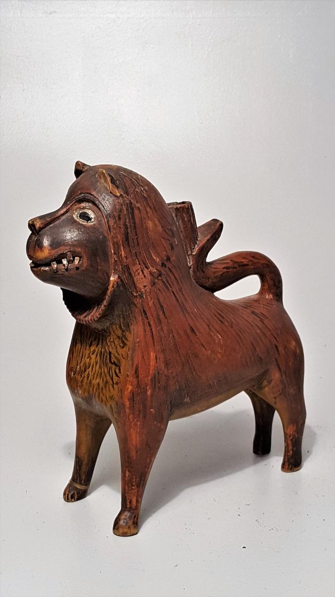 """Form: Som utskoren løve 1 """"lysestake av træ, """"dyrestake""""  En lysestake av form som en utskaaret løve med lysholder mellem den paa ryggen liggende hale og manken. Ligner """"Lys og lysstel"""" 176. Løven er malet rødbrun med gule og sorte chatteringer. Stammer formentlig fra Sætersdalen; herom kunde sælgeren ingen beskjed gi. Kjøpt av antikvitetshandler Alfred Andersen, Bergen."""