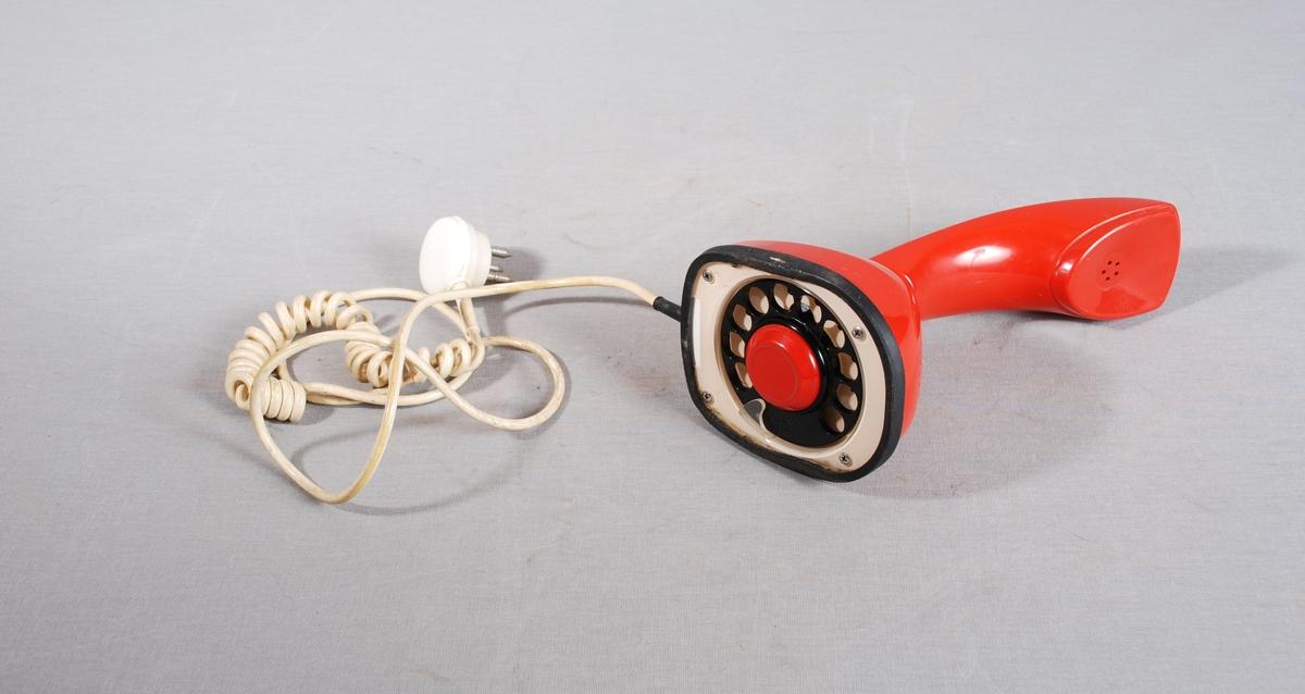 Analog bordtelefon med tallskive og av/på knapp i bunnen. Mikrofon og høyttaler i ett stykke. Spiralledning med trepinns kontakt.