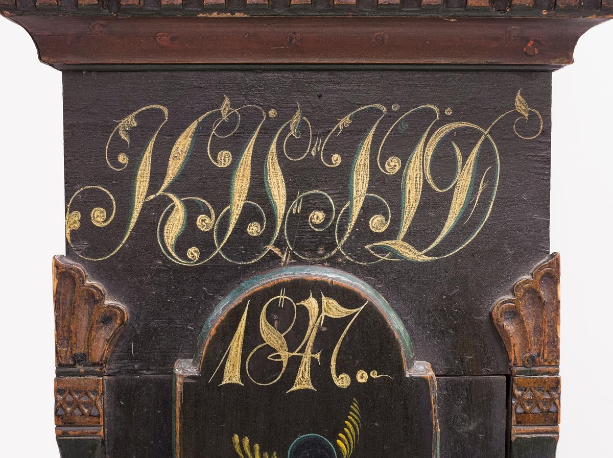 """Klokkeskap fra gården Jonshegge i Øystre Slidre med karakteristiske empiretrekk. Base med speilfylling i rødt og blått. Slank korpus med halvsøyler med plametter i ytre hjørner, og skapdør med fint malt urnemotiv. Klokkeskapets topp hviler på utkragende profilerte lister. Midterste list har tannbord i gull. Klokkeskapets dør er ellers utformet med halvsøyler i ytre hjørner, runde """"prikke""""-motiv og buerundt vindu. Klokkeskapet avsluttes med kraftig gjennomskåret grind."""