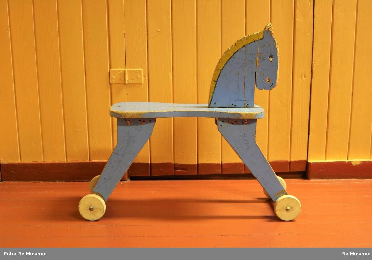 Leikehest med fire hjul og sete til å sitte på. Hovudet til hesten har munn, nasebor og øyre som er utskore. Auger og man er måla. Leika er tydeleg prega av bruk og målinga er avsliten fleire stader. Skruvane som som festar beina til setet ser ut til å vera nyare.