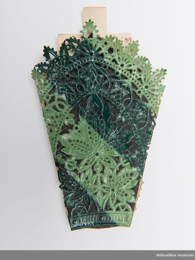 """Präglat papper, randigt i två gröna nyanser vikt runt ett kors med tryckt blommönster. Svart mellanpapper med vitt tryck. I mellanpapperet en rosbild, ett altare med kors och ett vilalande lamm, därovan en stjärna. Text på korsets baksida: """"Farfar död d 4 juni 1913, begrafn d 7 juni"""" På kortets baksida: """"Farfar död d 4/6 13 Begrafning d 7/6 1913"""""""