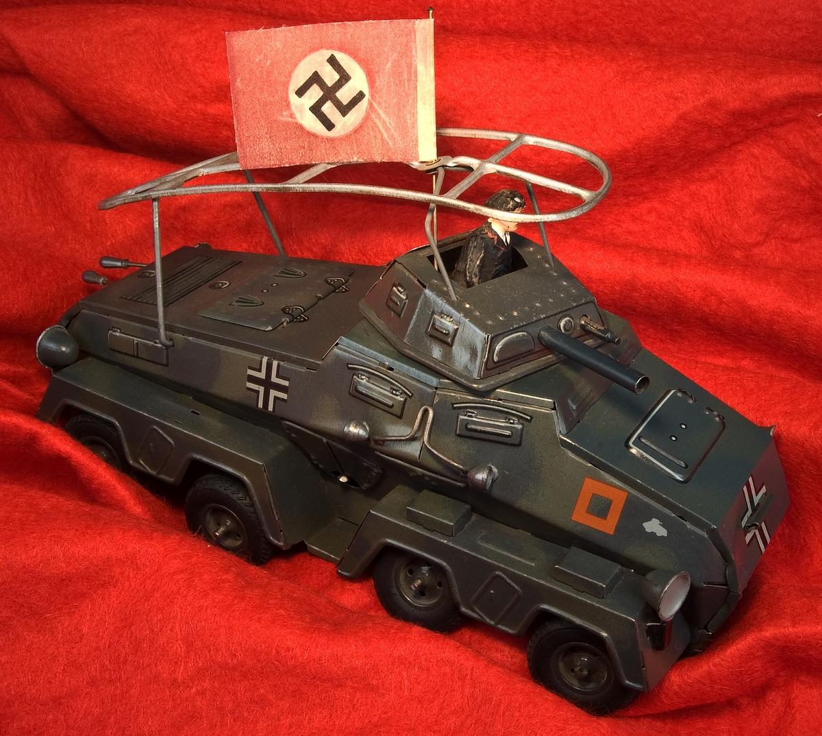Leksaksstridsvagn av lithograferad plåt. Mörkt grön med dekorationer i rött och vit/svart. Okänd tillverkning. Saknar stämplar. Till stridsvagnen finns en soldat, förmodligen av elastolin, en nazistflagga samt en nyckel för uppskruvning.