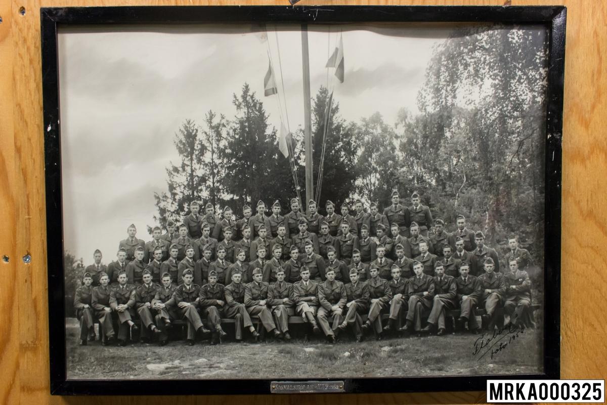 Fotografi taget på befäl och soldater som genomfört grundläggande soldatutbildning på 1:a Batteriet KA 2. Fotografiet taget vid Signalskolan på Gräsvik KA 2. Flobergs Foto 1952.