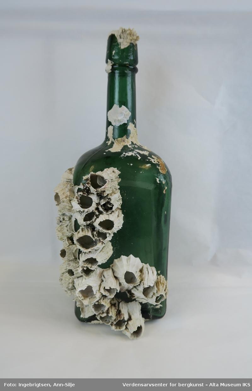 Form: Firkantet med avrundet tut. På to av sidene er det grodd kalkalger fast på flaska.