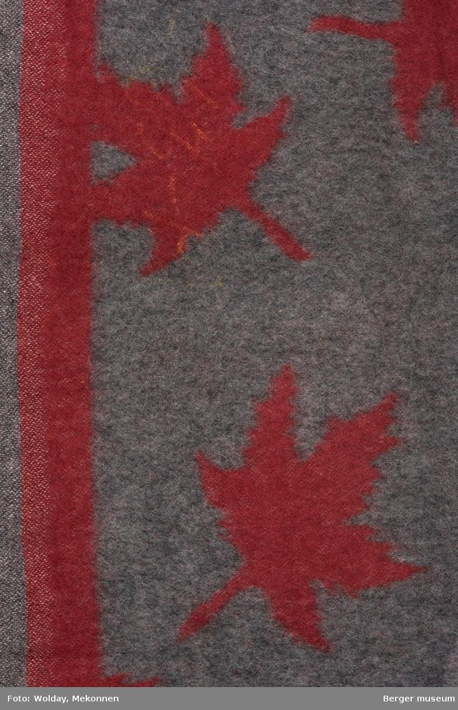 Et langt, tofarget pleddstykke med store enfargete lønnebladmønster. Jarekant på lansiden. Stykket har avklippete biter. Fargene er  invertert på for- og bakside.