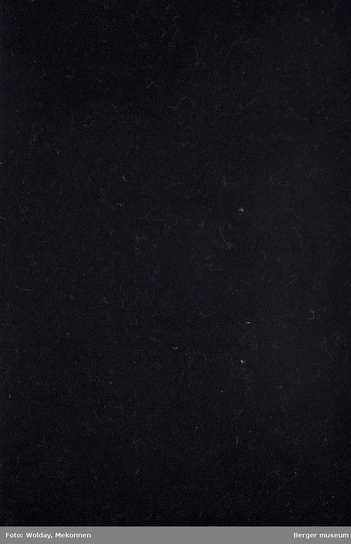 Ensfarget tekstilbit, med klippete kanter, ene kortside med frynser.