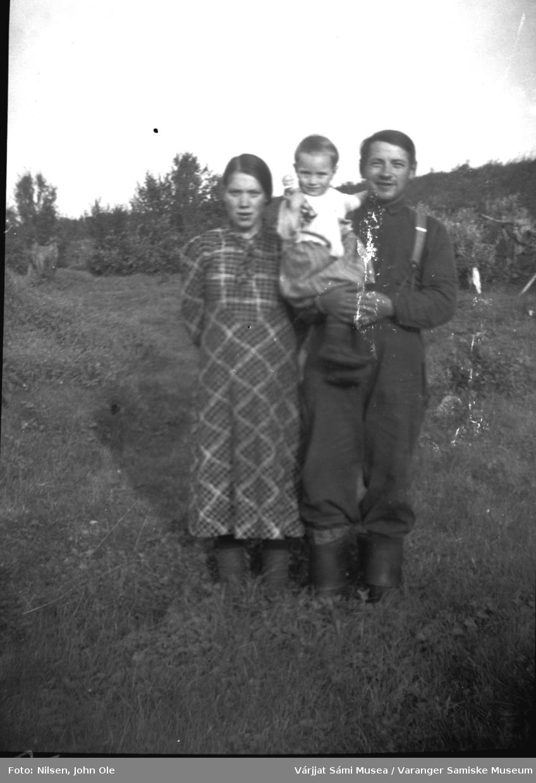 Gruppebilde utendørs. En kvinne og en mann som holder et lite barn. Barnet holde ren dukke. Mannen er Johan (Jonte) Roska. Muligens Fuoitnjárga / Bunes på 1940 tallet.