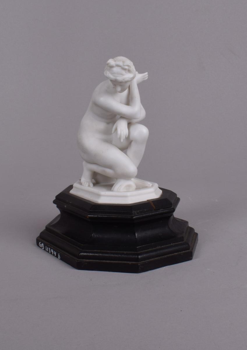 Naken, klassisk kvinne som sitter på en vase, og med kneet på et skjell.