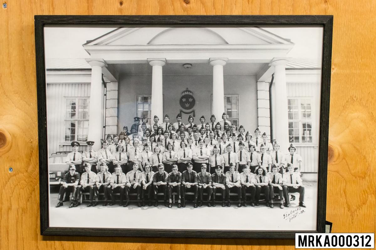 Fotografi taget på befäl och soldater som genomfört grundläggande soldatutbildning på 1:a Batteriet KA 2. Fotografiet taget utanför gymnastikhallen på Gräsvik KA 2. Flobergs Foto 1977.