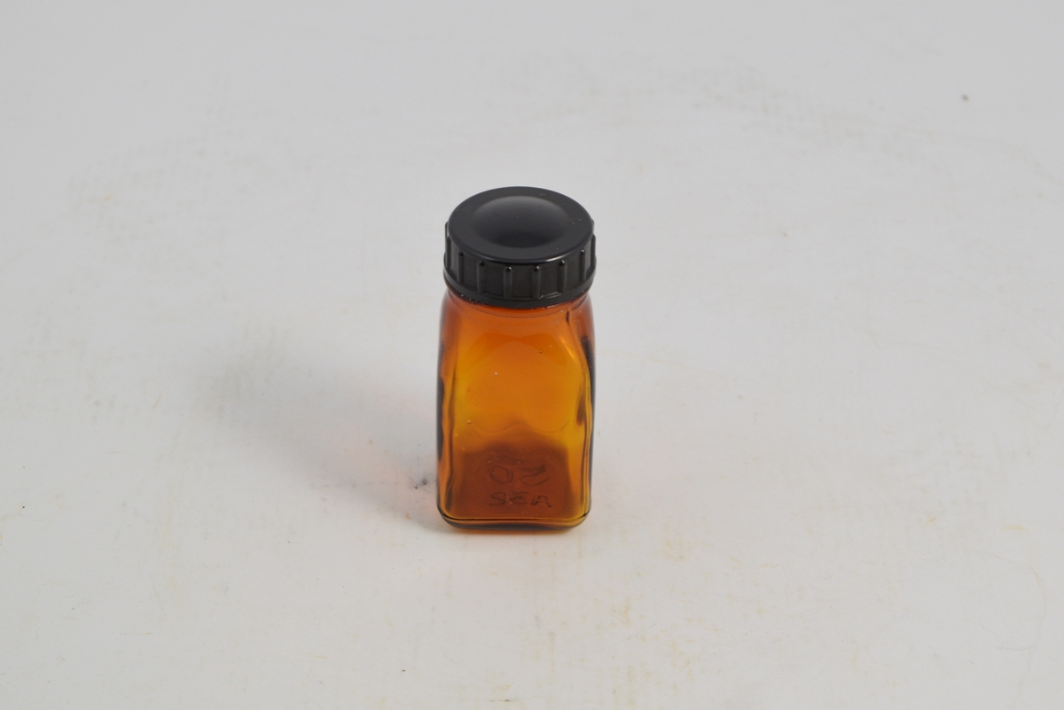 Brun transparent firkantet tablettglass med sort rundt bakelittlokk, skru. Brukt til oppbevaring og salg av tabletter, ca. 1950-1960.