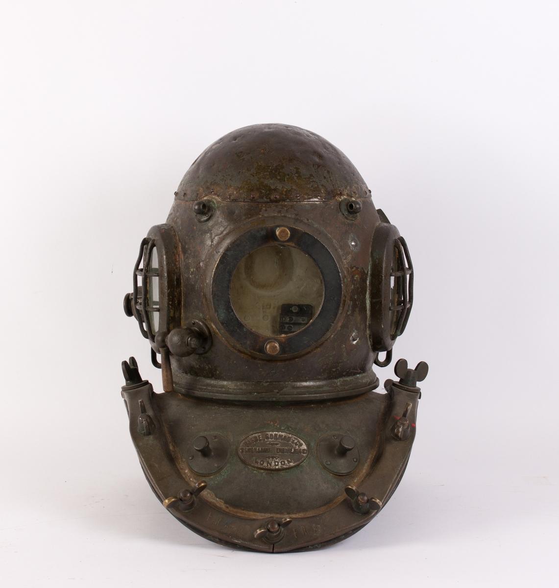Dykkerhjelm i kobber med to glassåpninger med gitter på siden samt en glassventil uten gitter som kan åpnes i front. Luftinntak i bakre del av hjelmen. Hjelmen er skrudd sammen med en kravekant som går utover skuldrene med 12 stk. vingemuttere.