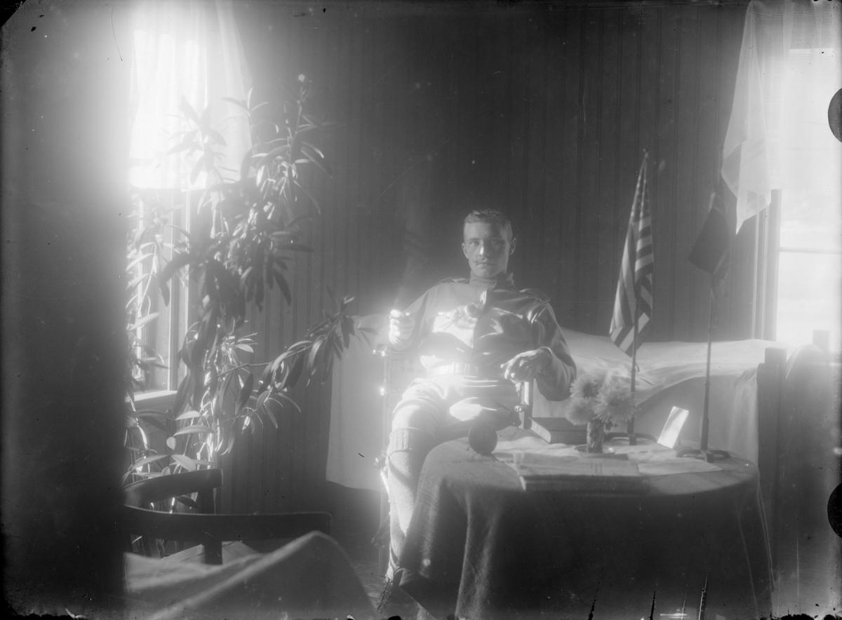 Mann ved bord med to flagg (Norge og USA) - i stua hos Mathea Baadstø