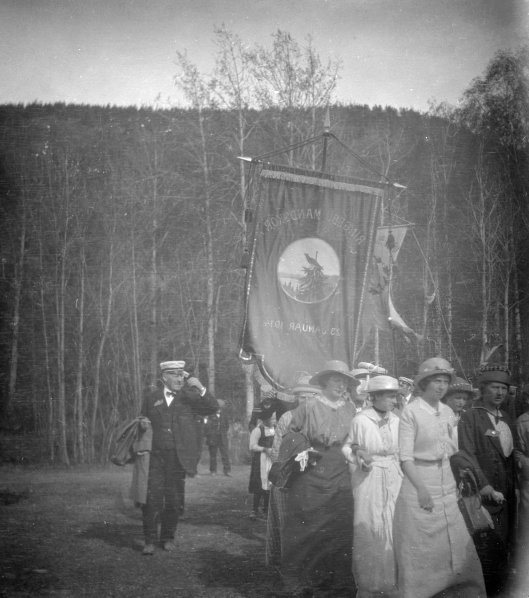 Kvinner i spissen for opptog. Bak fane med påskrift Ringebu Mandskor 23 januar 1914. Negativet halvert