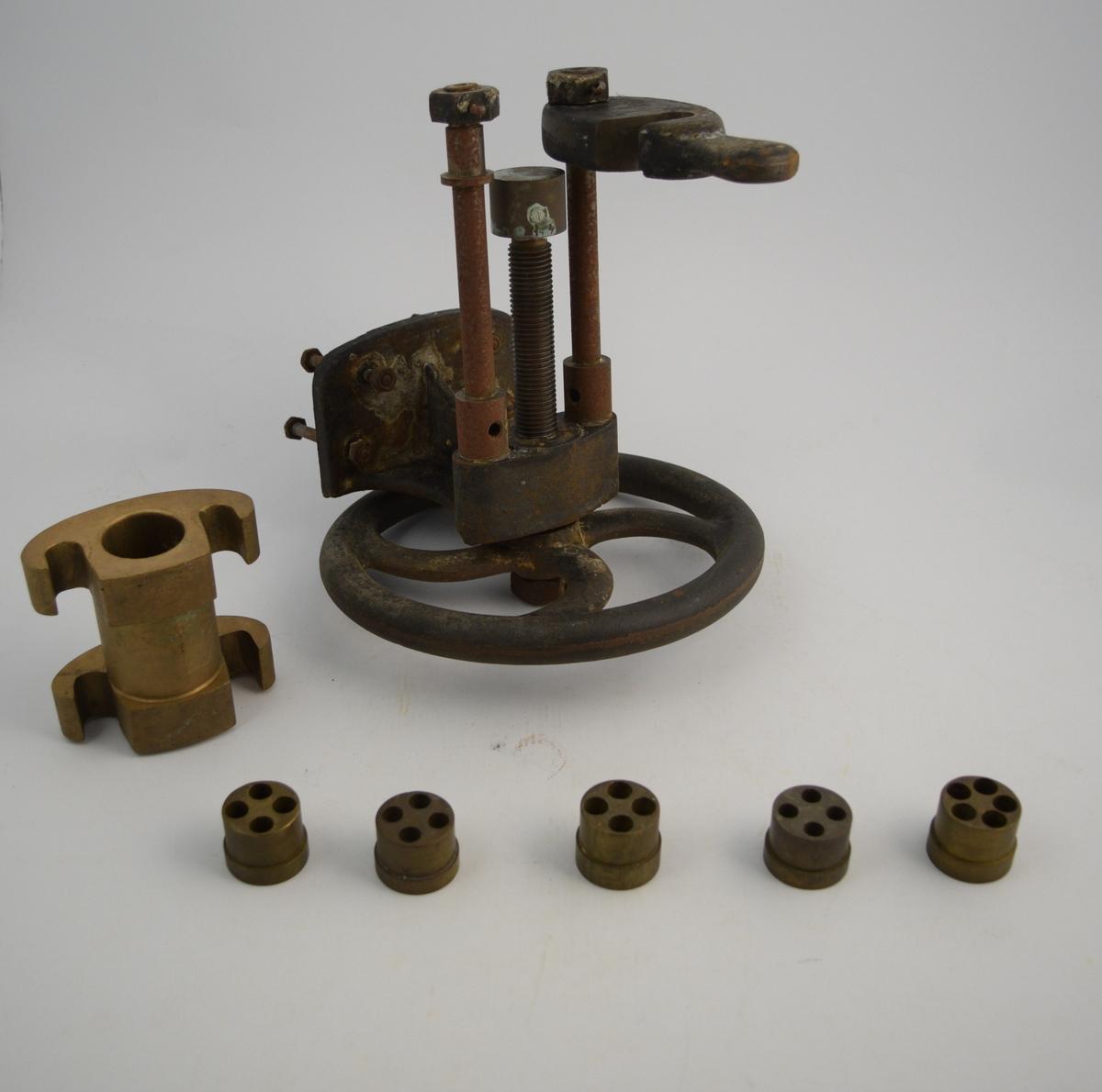 Stikkpillemaskin med 7 deler.  a) Selve maskinen med presse (jern). Stort hjul m/3 sylindre, 1 m/gjenger. Skrumekanisme.  b) Holder for stikkpillemasse og from (messing). Sylindrisk hull.  c-g) Former for stikkpillene, forskjellig størrelse (messing).  Brukt til produksjon av stikkpiller på apotek.