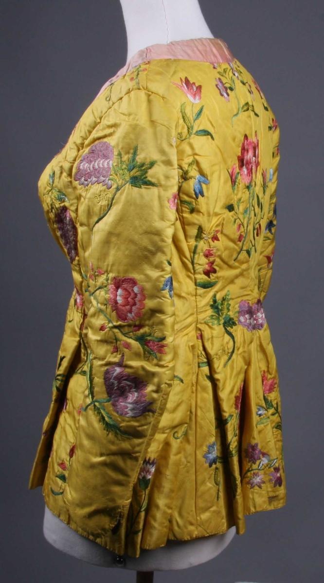 Av gul taft med polykrome blomsterbroderier: tulipaner, nelliker, roser, drueklaser etc. i rødt, blått, grønt og fiolett i flere nyanser og litt hvitt, gult og brunt. Broderiet er utført med silketråd i plattsøm og silkesting. Jakken er ringet utover skuldrene og ned i spiss foran, den er lukket med messinghekter. Den har skjøt nedentil som er sterkt utsvinget, særlig i ryggen. Forstykkene er senere sydd inn i livet ved hjelp av legg, og trøyen er også tatt inn i midtsømmen i ryggen. Ermene er lange og trange, underarmsømmen er sterkt buet og ved isyingen er ermet plassert høyt oppe på brystet. Under armen er innfelt et stykke som nederst skrår ut til full bredde av ermet. På utsiden av ermet er det søm fra albuen og ned med splitt nederst. Langs halsen er påsydd et rosa silkebånd og antagelig har det vært et tilsvarende på ermene litt overfor kanten. Fôr i selve trøyen, og ermene av rødt ullstoff, i skjøtet av gult, vokset lerret, og likeså i ermåpningene.
