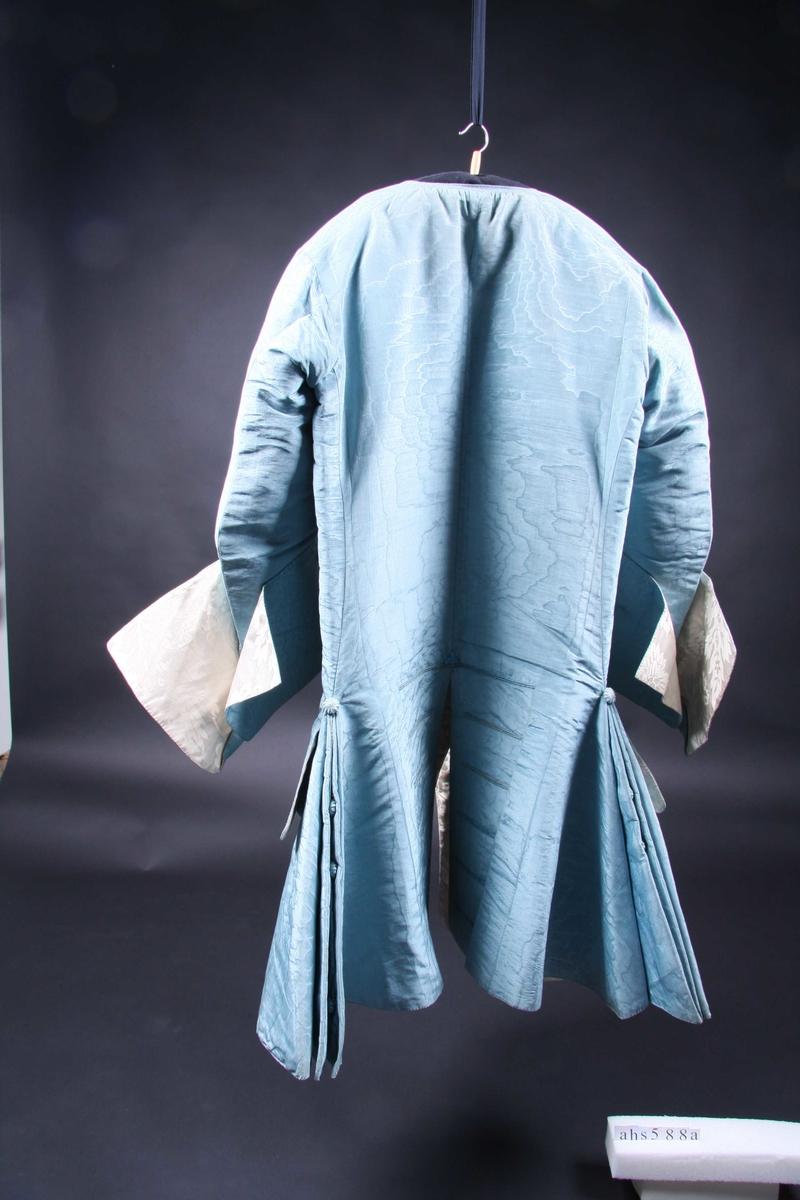 Del av herredrakt som består av frakk og ermeløs vest, betydelig kortere enn frakken. Begge er av mellomblå silkemoiré, nå en del falmet. Frakken har helt fôr av hvit silkedamask med stort blomster- og bladmønster. Den er videre sterkt utskrådd i sidene med stor vidde nede, forstykket og skjøtet er klippet i ett. Foldene i siden er festet sammen, utspringet sitter litt nedenfor livet og er markert med en possement-knapp. Der er en possement-knapp inne i foldene nede og to som markerer en åpning i siden midt inne i foldene. Skjøtet er foran avstivet med papir-innlegg som også går oppover langs kanten av forstykket. Skjøtet er en tanke tilbakeskrådd i forkanten fra livet og ned. Lommene er skåret inn i stoffet, lommeklaffene er store, uttunget i kanten og sitter i høyde med foldeutspringet. De er forsynt med fire 12 cm. lange knapphull hvorav de to midterste er blindknapphull, og fire possement-knapper på lommen. Forstykkene er tett besatt langs kanten med samme slags knapper, 15 i alt, og på det annet blindknapphull, unntatt nr. 2 ovenfra som kan knappes. Knapphullene er 10,5 cm. lange, noe kortere nederst på forstykket. Ryggen har splitt nederst med to delvis nedsydde folder på sidene og en rad av 6 blindknapphull på hver side. Den har søm langs midten, er ubetydelig innsvinget i sidene og skjøtet er klippet i ett medd hver rygghalvdel. I halsen er det en smal linning av stoffet. Ermene er 3/4 lange med svære åpne mansjetter, fire possement-knapper og blindknapphull vertikalt på overkanten. Ermene er fôret med hvitt linlerret, mansjettene derimot med den hvite silkedamasken som frakken ellers.