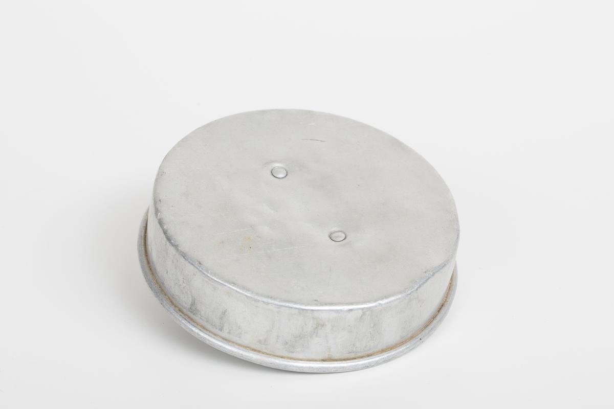 Lokk til melkespann for bruk i husholdning. I aluminium. Det er et lite håndtak på lokket.