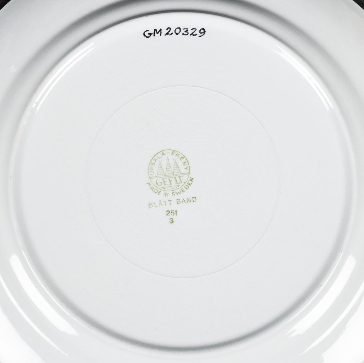 """Tallrik, flat, av flintgods, modell -F, formgiven av Arthur Percy för Gefle Porslinsfabrik. Låg med stor spegel och liten bräm, stor fotring. Dekor """"Blått Band"""" med handmålad, blå bladrosett på blåtonad fond. Blått band efter kant. Dekor av Percy. Grön skorstensstämpel under med text """"Upsala-Ekeby Gefle Made in Sweden Blått Band 251/3""""."""