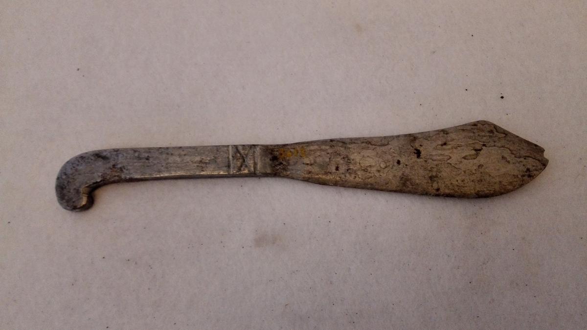 1 bordkniv av staal  Hjemmesmedet bordkniv, hvor model er tat efter de messingskjæftede foldeknive. Kniven skal være smidd av en Dominikus Ørbech i Natviken. Gave fra Ivar E. Offerdal, Ofredal.